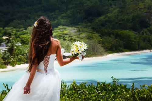 Bride overlooking bay and the beach