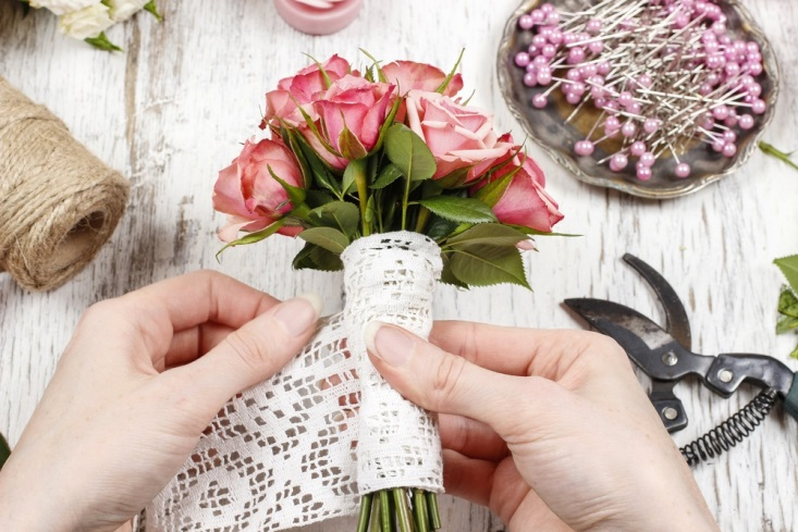 How to plan a wedding on a budget wedsafe wedding insurance florist wrapping a small bouquet of pink roses with lace junglespirit Choice Image