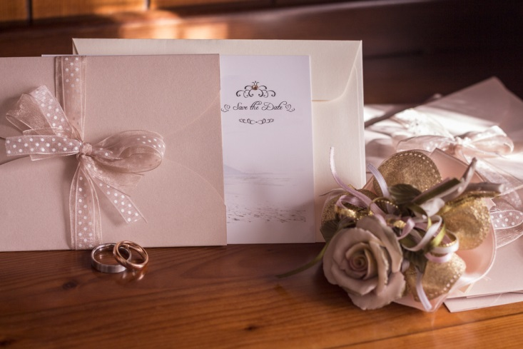 Taupe save-the-date cards, two wedding bands, and a bouquet of flowers