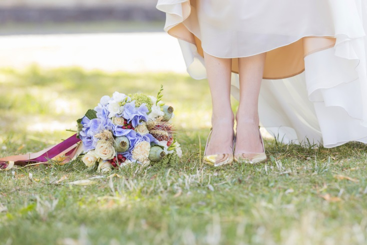 Bride holding up her dress to show off her shoes next to her bouquet