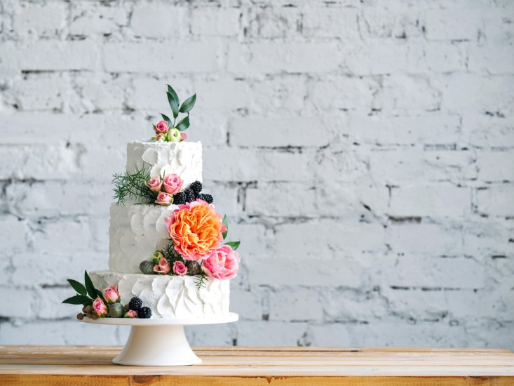 Wedding cake on wooden table in front of white-washed brick wall