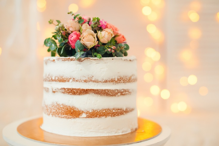 Wedding cake with light icing and real flowers on top