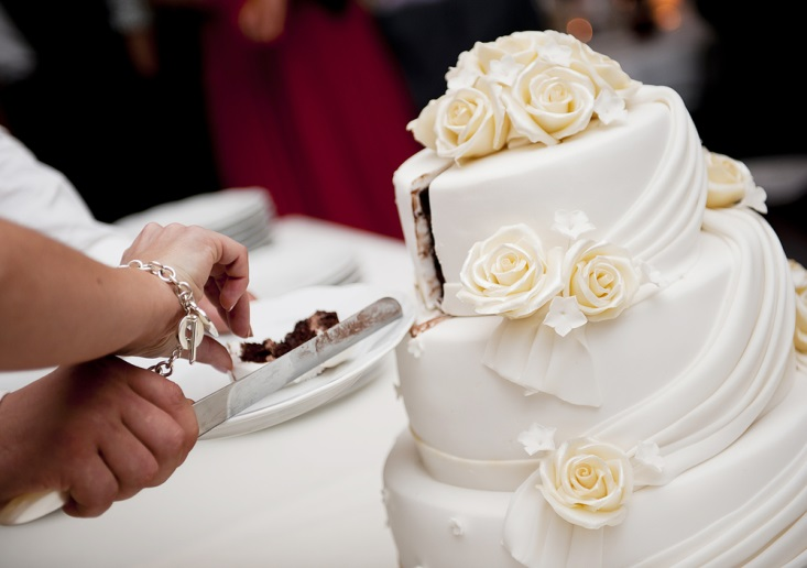 Bride and groom cutting their exquisite white and red wedding cake
