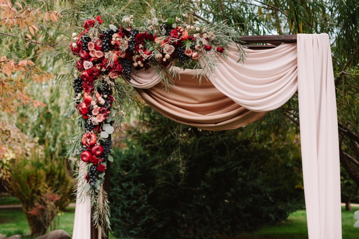 Arbor decorated with apples and pears for fall-inspired wedding