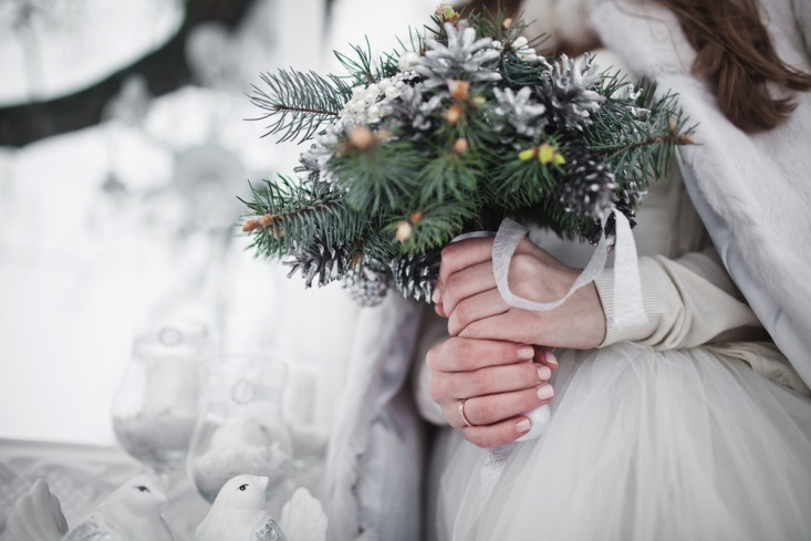 Bride's hands holding a winter-inspired bouquet