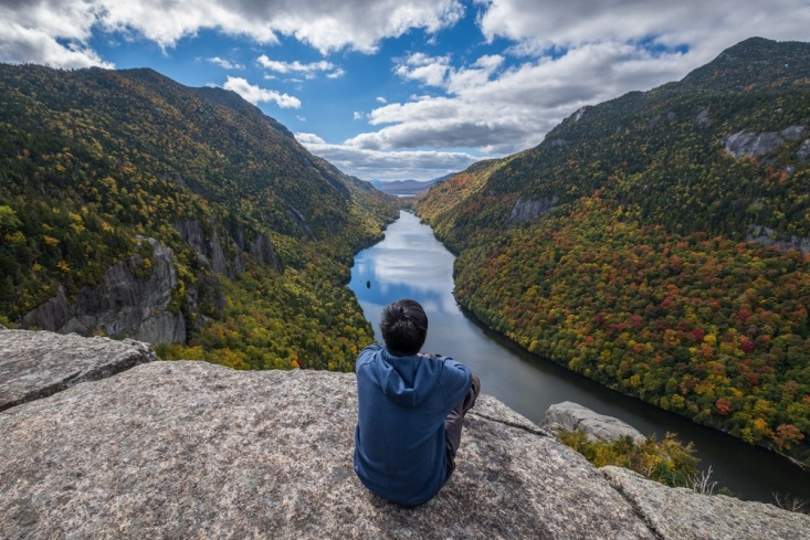Man sitting on edge of cliff and surveying the breathtaking views of the Adirondacks in New York