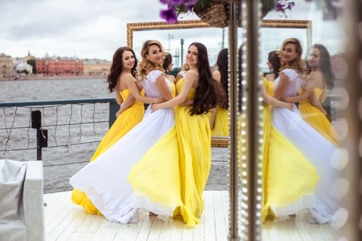 Bride and two bridesmaids in yellow dresses smiling on dock at waterside wedding