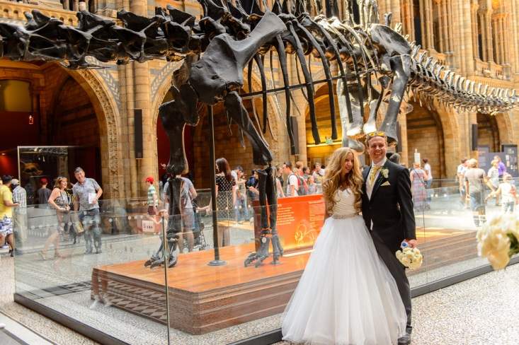 Newly married couple posing in front of dinosour fossil at their museum wedding