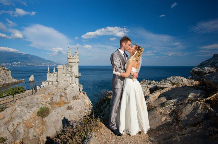 Newly married couple kissing at their outdoor venue by a castle on the coast