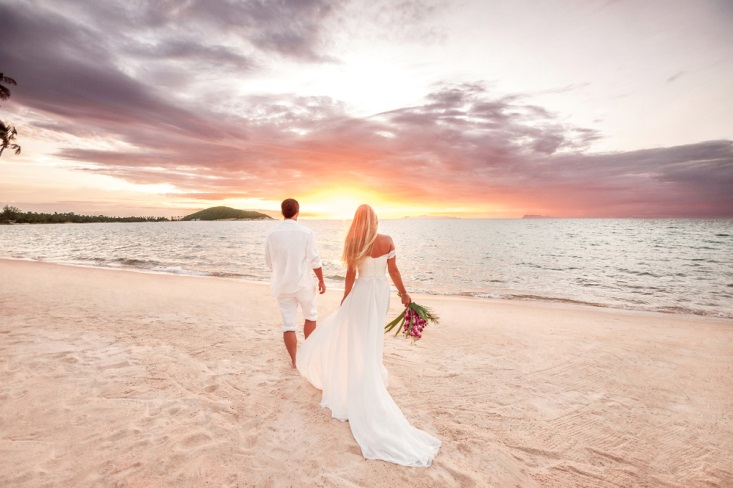 Beautiful bride and groom watching the sunset over the ocean